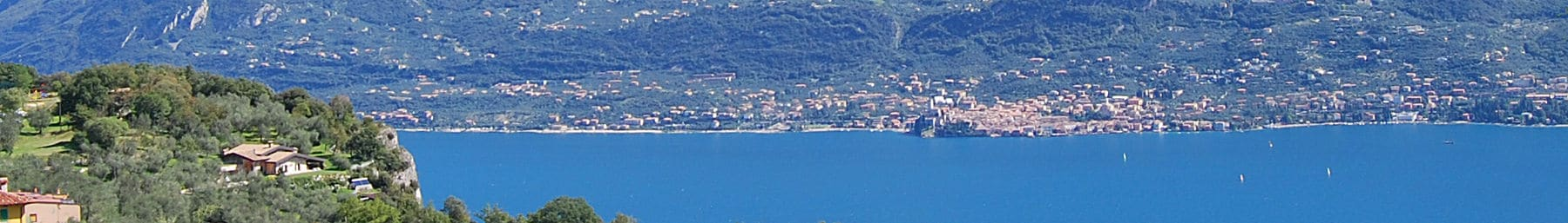 1800px-Lake_Garda_banner_Coast_across_lake